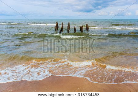 Wooden Piles Of An Old Pier Near The Sandy Shore In The Baltic Sea Near The Latvian Village Of Jurka