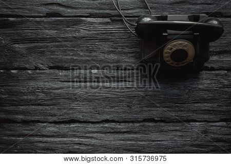 Black Old Rotary Phone On A Black Wooden Table Flat Lay Background With Copy Space. Contact Us.