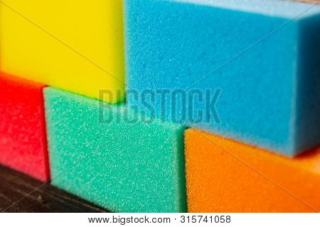 Sponges Of Different Colors In Dark Background Forming A Wall. Pieces Of Dishcloth Laid As Bricks On