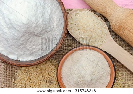 Whole grain rice flour and white rice flour in bowls. White rice, brown rice. The whole grain of rice. Polished rice in wooden spoon. Healthy food rice background. Row rice. Rice flour. Rice flour baking. Brown rice flour.