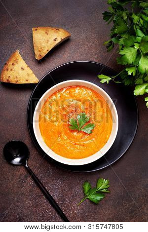Vegetable Soup In A White Bowl On A Blrown Background. View From Above