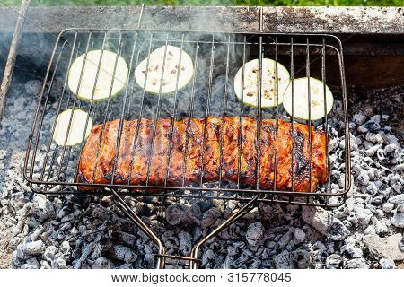 Cooked Pork Ribs With Sliced Zucchini Vegetable In Outdoor Charcoal Grill