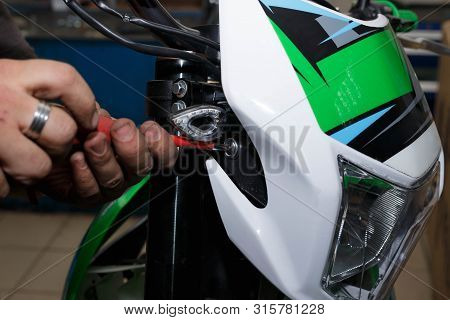Installing The Front Lamp With A Plastic Lining On The Motorcycle.