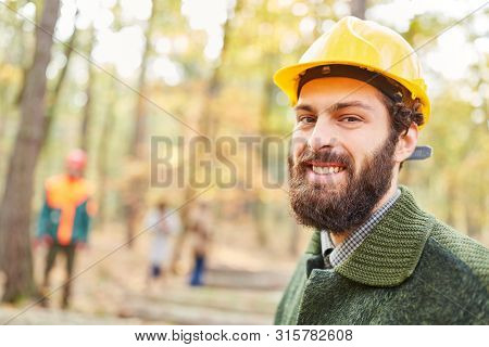 Forest worker or forestry worker smiles contentedly while working in the forest
