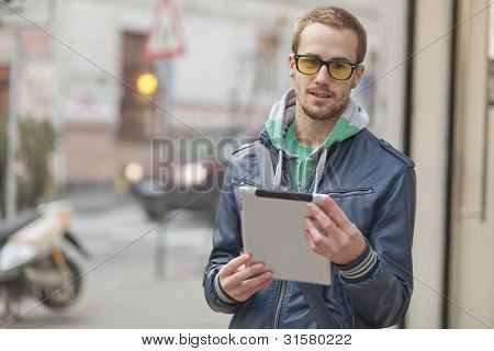 Young man with yellow glasses use iPad tablet computer on street public space. Blurred background poster