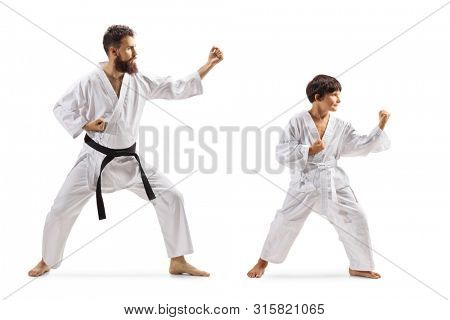 Full length shot of a boy and man in kimonos practicing karate isolated on white background