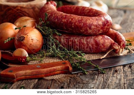 Dry-cured Sausage With Thyme, Onion, Garlic And Pepper. Sausage With Bread And Spices On A Old Woode