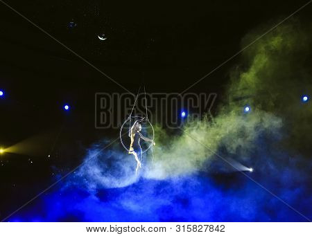 Aerial Acrobat In The Ring. A Young Girl Performs The Acrobatic Elements In The Air Ring