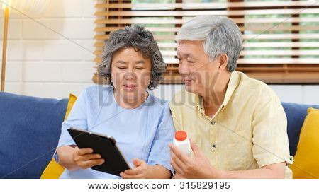 Senior Asian Couple Holding Bottle Of Pill Using Digital Tablet To Make Video Conference Call To Doc