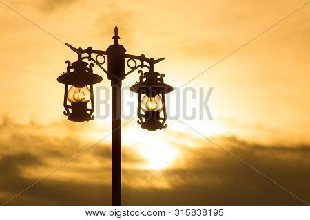 Silhouette Wrought Iron Street Lamp At Sunset