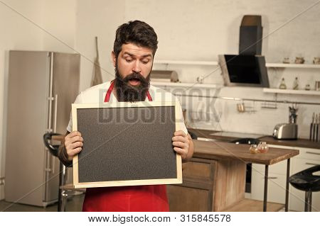poster of Secret tips. Useful information. Man bearded hipster red apron stand in kitchen. Kitchen furniture store. Kitchen hacks concept. Clever ways to organize kitchen. Cook hold blank chalkboard copy space.