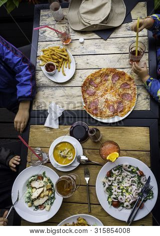 Top View Family Dinner On Wooden Table: Eating Foods Salad With Shrimps, Soup With Sea Food, Pizza,
