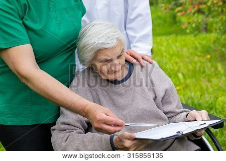 Aged Woman With Dementia Sitting In A Wheelchair, Male Doctor And Female Nurse Taking Care Of Her Ou
