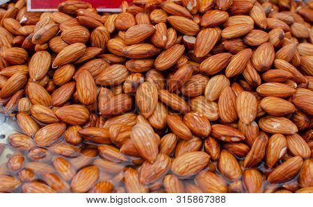 almonds soaked in water  for sale at farmers market poster