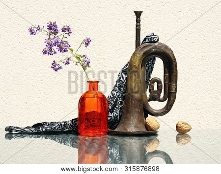 Still Life With Flower In Vintage Glass Bottle, Two Whole Walnuts And Old Rusty Bugle Against A High