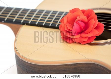Love Song. Red Rose On Acoustic Guitar. Romantic Music Concept. Close Up Of Beautiful Flower On Qual