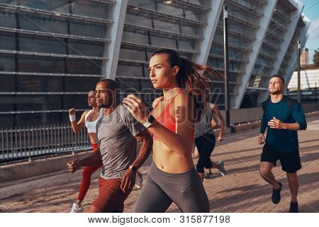Group Of Young People In Sports Clothing Jogging Together Outdoors