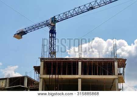 Industrial Crane Near Building Against Blue Sky. Construction Site. Industrial Background.