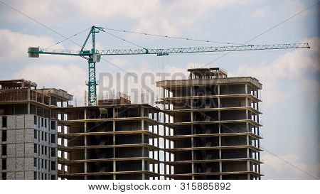 Construction Site Background. Hoisting Cranes And New Multi-storey Buildings. I.ndustrial Background