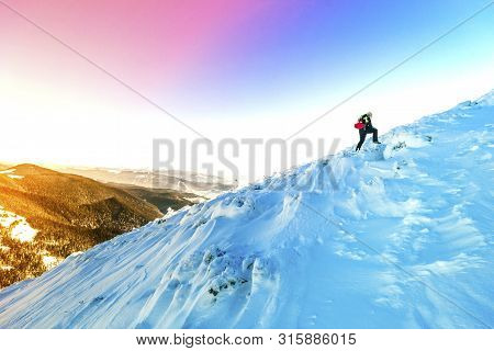 A Male Mountaineer Walking Uphill On A Glacier. Mountaineer Reaches The Top Of A Snowy Mountain In A