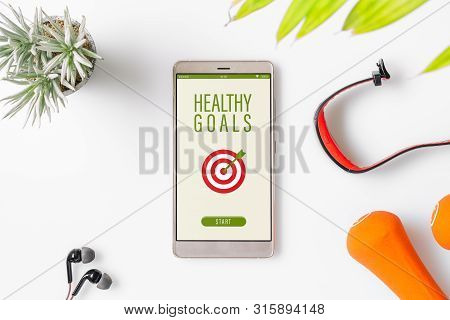 Healthy Goals Concept. Fitness Healthy Goals With Mockup Mobile Phone On White Table With Dumbbells,