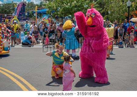 Orlando, Florida. July 30, 2019. Telly Monster, Dancer Woman And Little Girl Playing In Sesame Stree