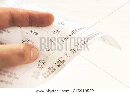 Human Fingers Holding A Paper Receipt With The Bill Of Charges And Checking The Total Amount. Domest