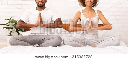 Tantric Connection. African American Couple Meditating In Lotus Position On Bed, Panorama