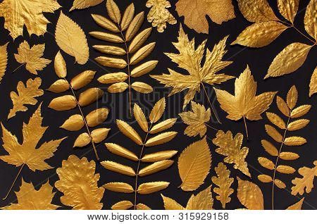 Flat Lay Creative Autumn Composition. Pattern Of Golden Leaves On Black Background Top View. Fall Co