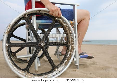 Detail Of A Special Wheelchair With Big Wheels To Move On The Sandy Beach Of The Resort With A Young