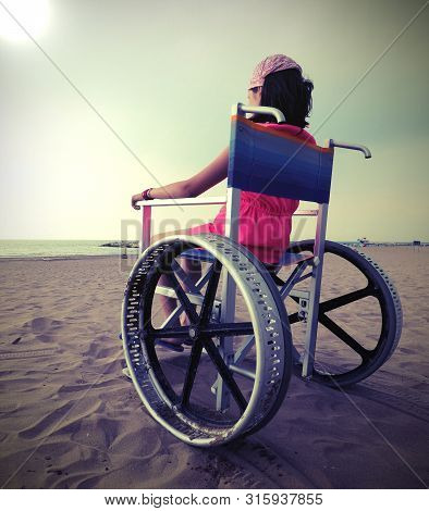 Little Girl On The Wheelchair With Big Wheels On The Sandy Beach In Summer With Old Vintqage Toned E