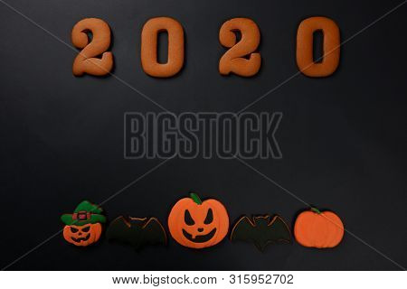 The hand-made eatable gingerbread 2020 inscription, Halloween pumpkins and bats on black background poster