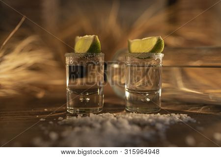 Two Shots Of Tequila With Lemon Slices And Salt Sprinkled By The Table- Luxurious And Delicious Tequ