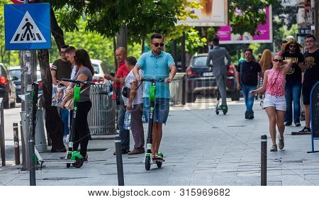 Bucharest, Romania - July 30, 2019: People Ride Lime-s Electric Scooters On A Sidewalk In Downtown B