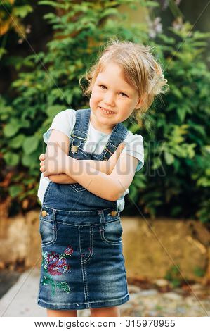 Outdoor Portrait Of Cute Little 3-4 Year Old Girl, Wearing Denim Pinafore