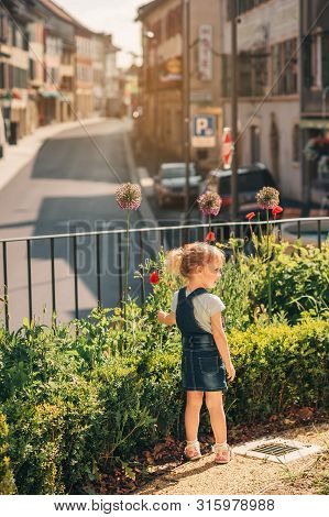 Outdoor Portrait Of Cute Little 3-4 Year Old Girl, Wearing Denim Pinafore, Playing In Public Garden