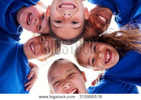 Low Angle View Looking Up Into Faces Of Children In Huddle On Sports Day