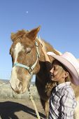 a young cowgirl shows caring and affection for her cute pony poster