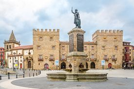 Gijon,spain - May 16,2019 - Statue Of Pelagius With Revillagigedo Palace In Gijon. Gijon Is Located