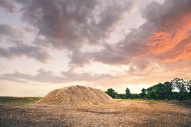 Mulch Pile In The Summer Sunset In A Rural Landscape With Dramatic Sky