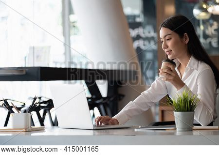 Remote Work. Asian Woman Working Remotely On Her Laptop. A Brunette Girl In A White Shirt Doing Note