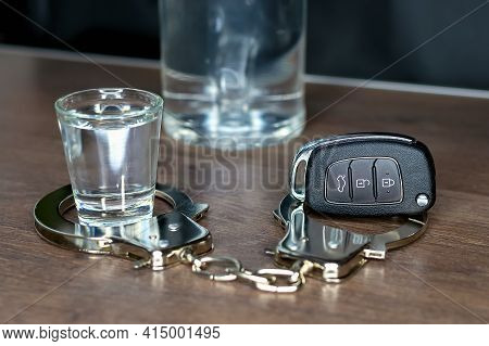 Close-up Of Car Key And Shot Glass Of Vodka With Metal Police Handcuffs And Bottle Of Alcohol On Dar
