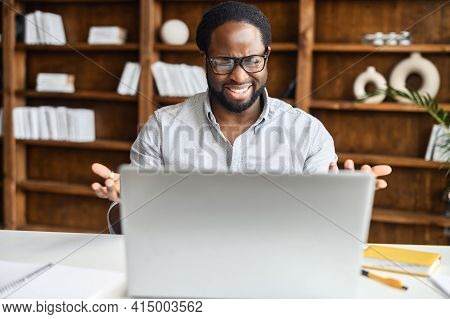 Confident Hispanic Man With Handsome Stubble, Talking In Front Of Computer, Wearing Blue Shirt, Talk