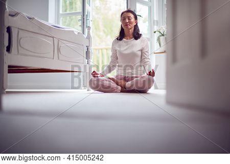 Mature Asian Woman In Pyjamas Sitting On Bedroom Floor Meditating In Yoga Pose