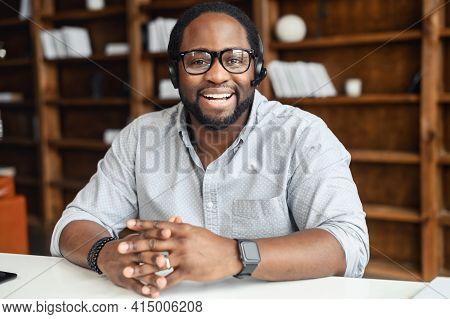 Smiling African Professional Telemarketer Call Center Operator Wear Wireless Headset, Looking At Cam