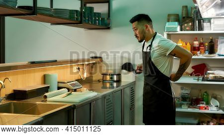 Young Man In An Apron Is Standing In Kitchen. Restaurant Work Concept. Bearded Chef Standing In The