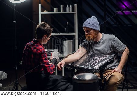 In A Modern Tattoo Parlor, A Girl With Piercings And Tattoos On Her Body Makes A Tattoo On The Bicep