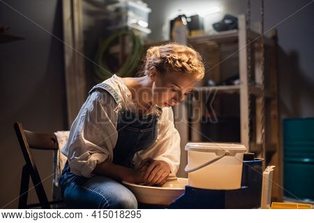 A Young Blonde Potter Girl Starts Making A Vase In Her Workshop On The Potters Wheel.