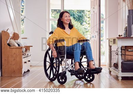 Mature Asian Woman In Wheelchair Pushing Herself Along Hallway At Home