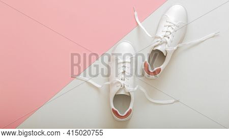 White Sneakers With Flying Laces, Female White Leather Shoes With Laces On Pink Background. Pair Of